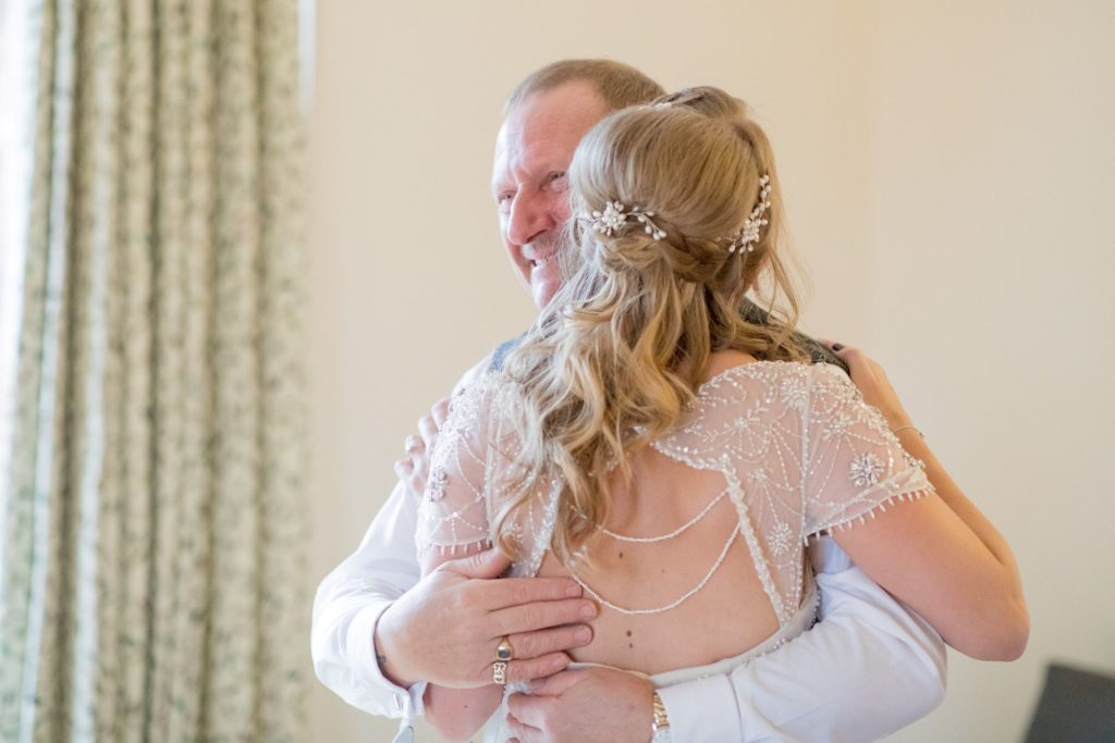 bride hugs father kingscote barn tetbury oxford wedding photographer