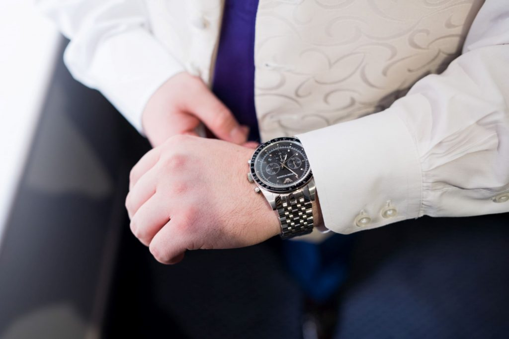 groom adjusts wrist watch sir christopher wren hotel windsor oxfordshire wedding photography