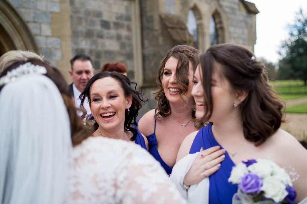 laughing bridesmaids greet just married bride royal chapel windsor great park berkshire oxfordshire wedding photographers