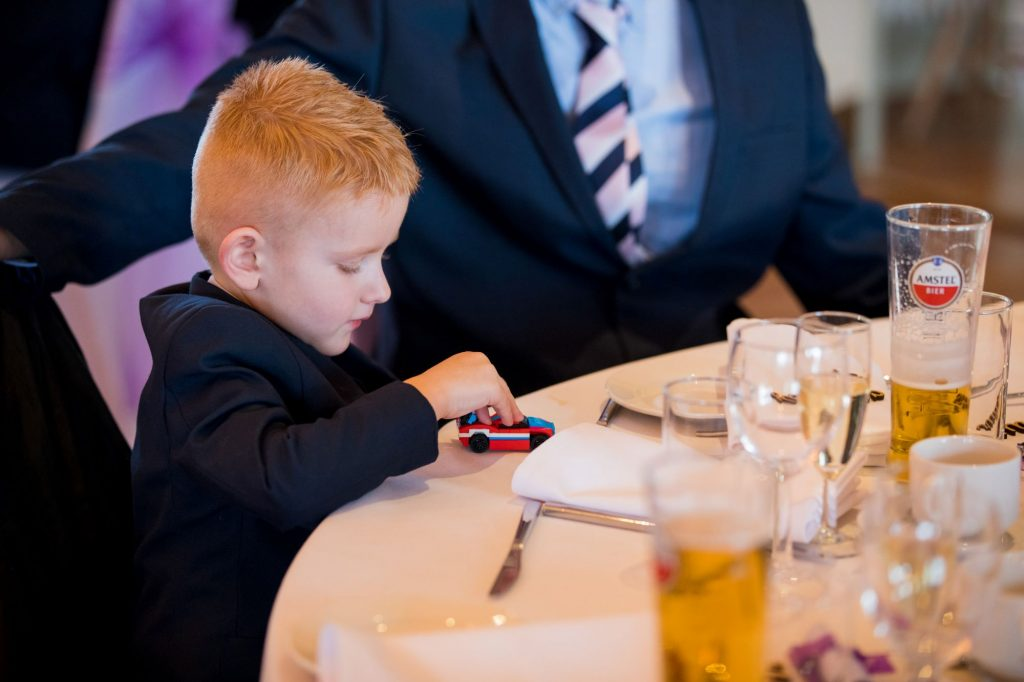 young boy plays during top table speeches york club windsor great park berkshire oxford wedding photography
