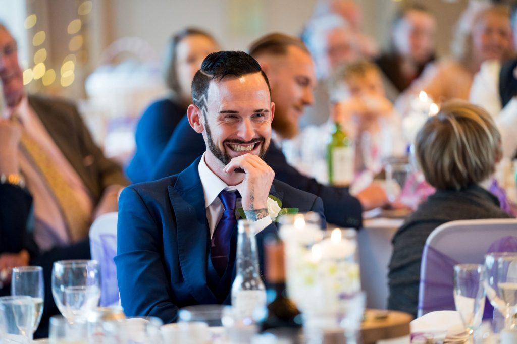 smiling groomsman hears bestmans speech york club windsor great park berkshire oxford wedding photographers