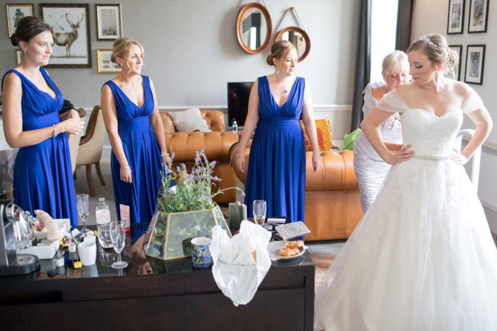 mother of the bride and bridesmaids help with dress bridal preparation de vere beaumont estate venue windsor berkshire oxford wedding photographer