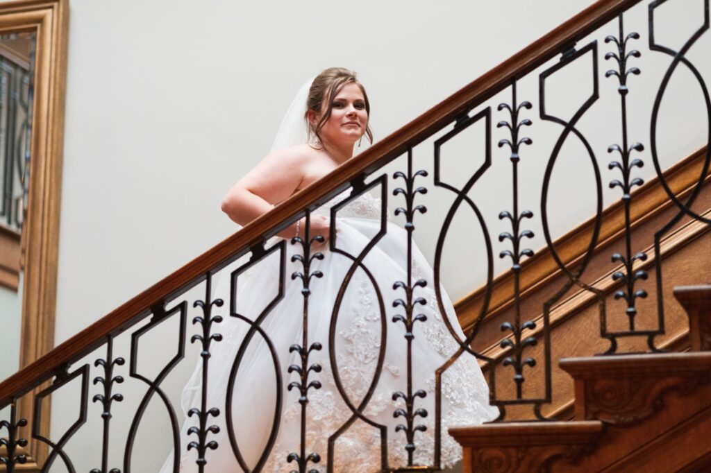 bride climbs stairs milton hill house hotel steventon oxfordshire wedding photography