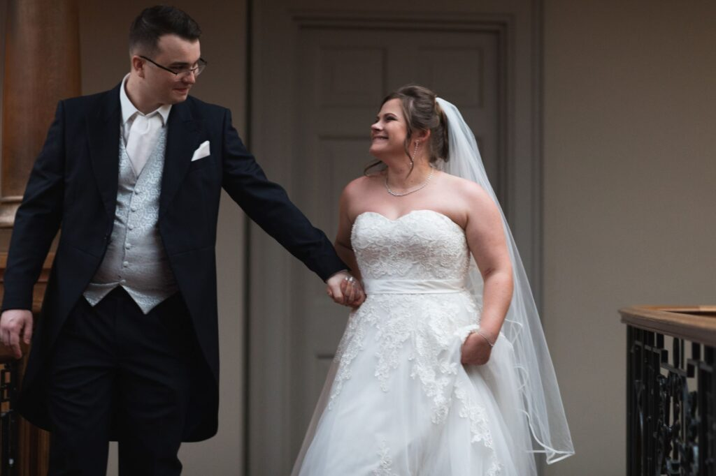smiling bride groom hold hands milton hill house hotel picture gallery steventon oxford wedding photographers