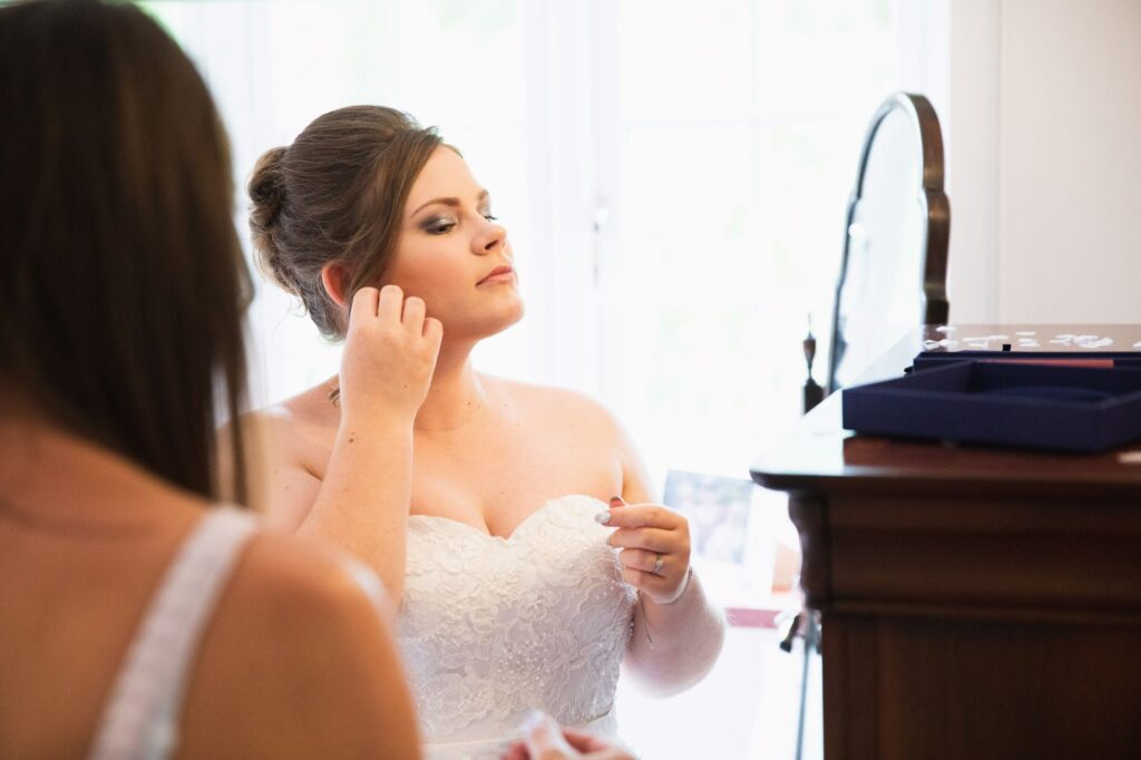 bride fixes earrings bridal prep streatley oxfordshire wedding photographers