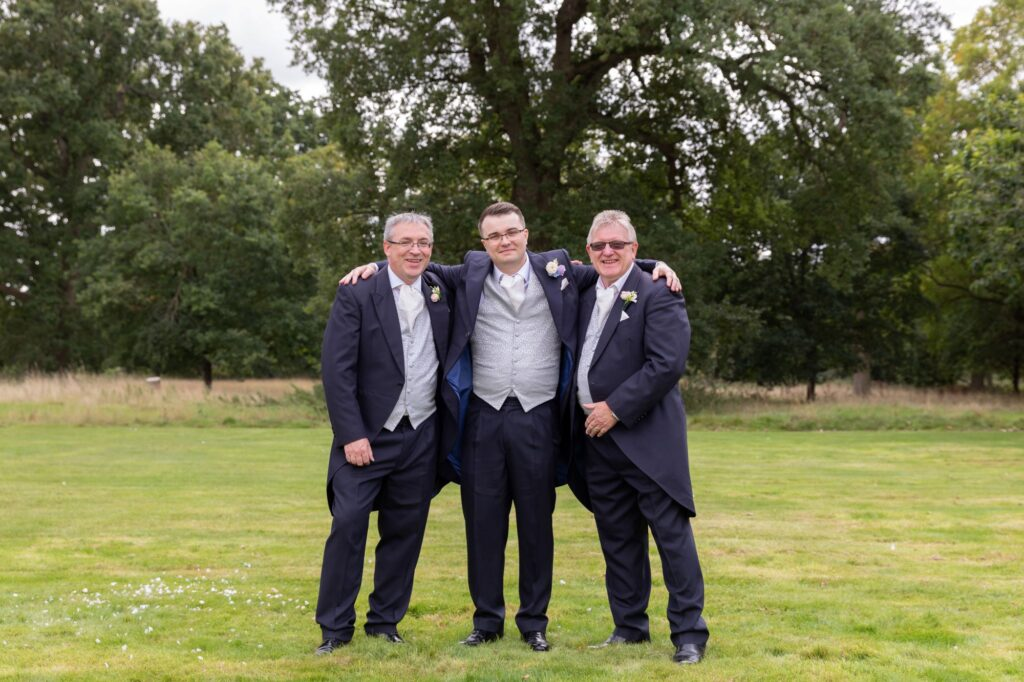 groom embraces family members milton hill house grounds steventon oxfordshire wedding photographers