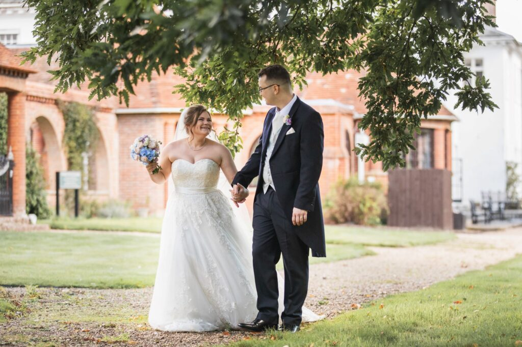 smiling bride groom hold hands milton hill house gardens steventon oxfordshire wedding photographers