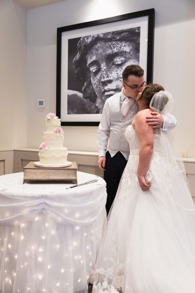 groom kisses bride cake cutting ceremony milton hill house steventon oxford wedding photographers