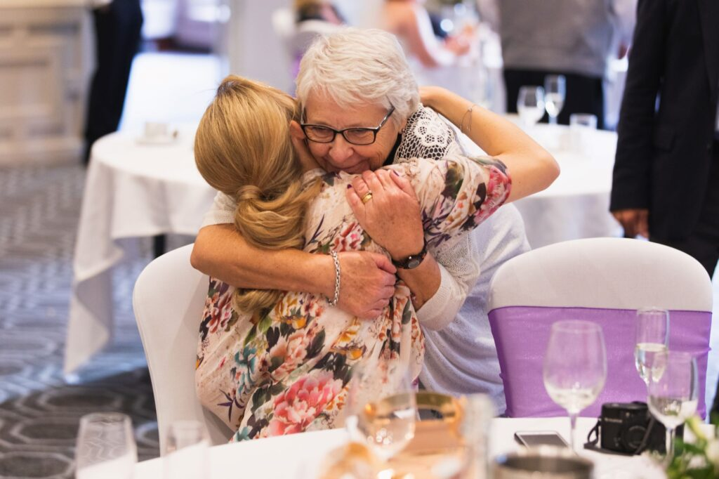 elderly guest hugs bridesmaid milton hill house reception steventon oxford wedding photographer