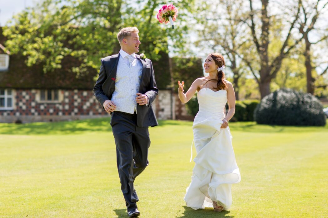 bride groom running throwing red flowers bouquet after marriage ceremony buckinghamshire venue oxfordshire wedding photography