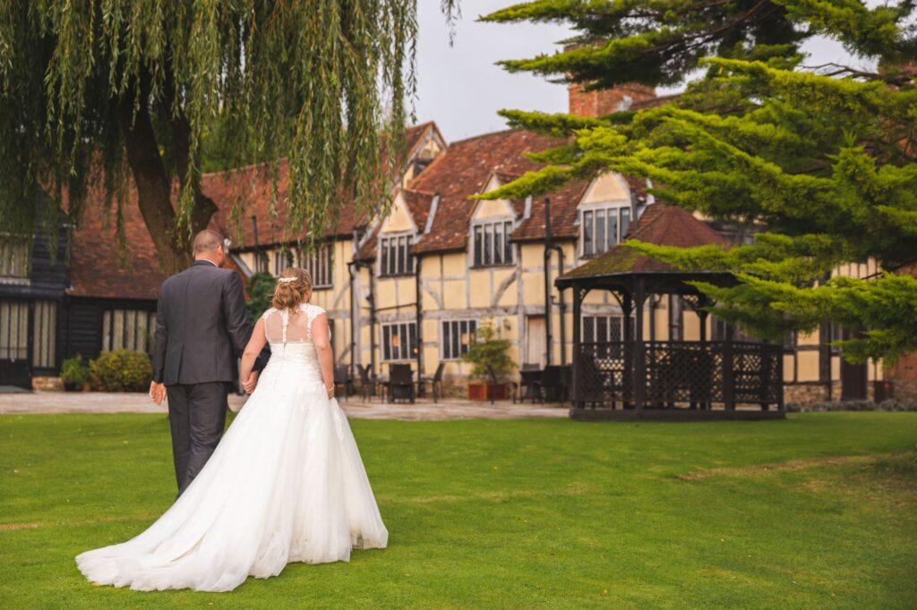 bride groom stroll towards cain manor surrey oxfordshire wedding photographer