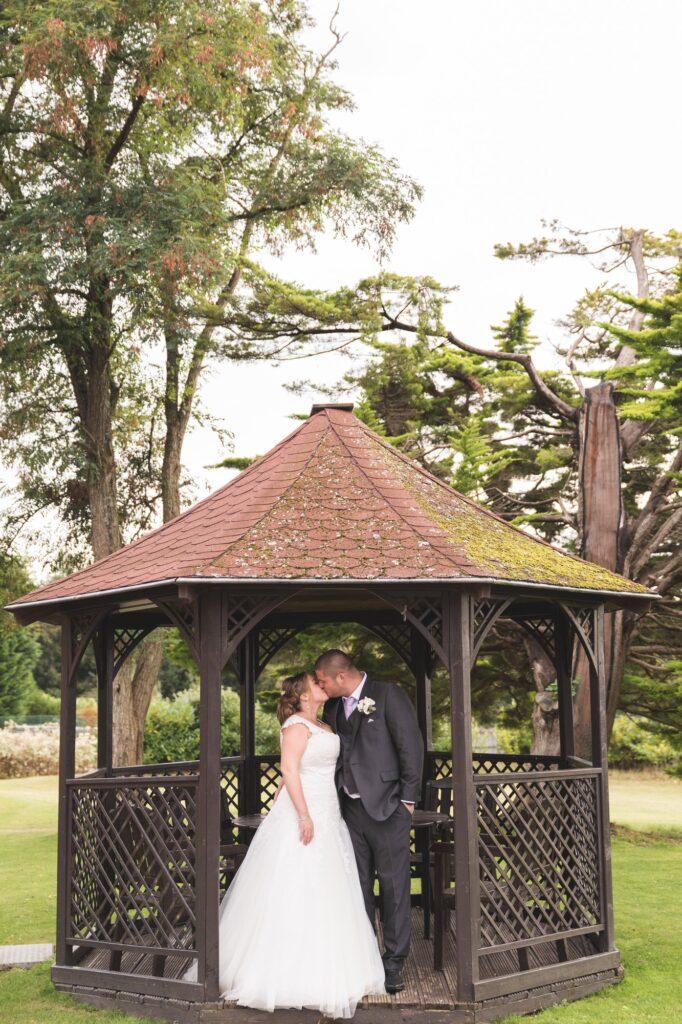 bride groom kiss under pergoda cain manor grounds surrey oxfordshire wedding photography