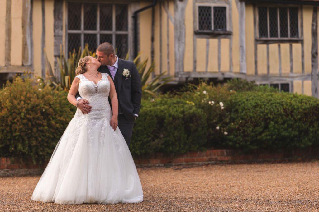 groom kisses bride outside cain manor hampshire surrey borders oxford wedding photographer