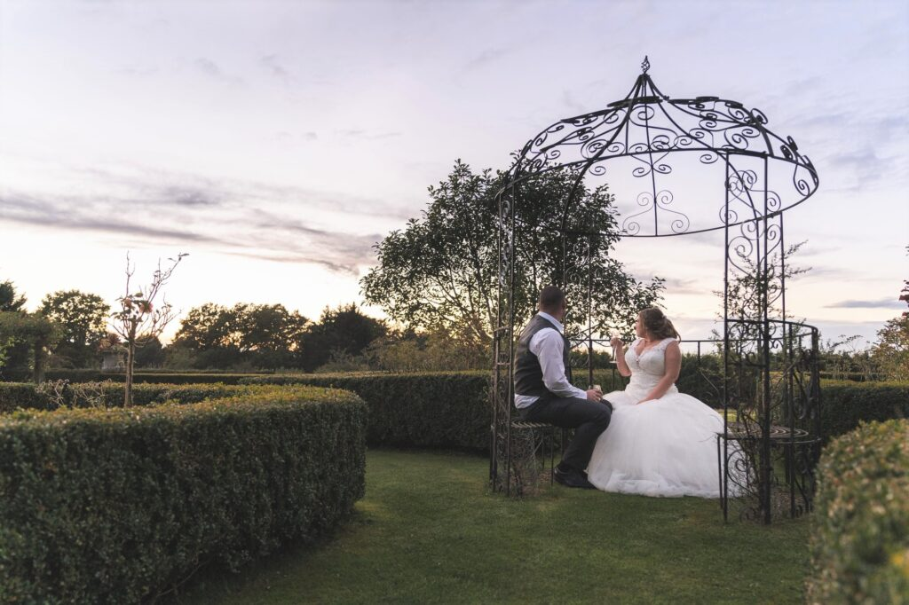 bride groom sip champagne at sunset cain manor gardens surrey oxford wedding photographer