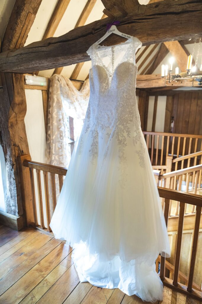 brides dress hangs exposed beams cain manor hampshire surrey borders oxfordshire wedding photography