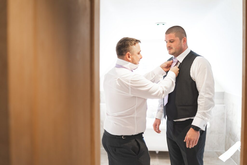 grooms tie fastened groom prep cain manor venue surrey oxford wedding photographer