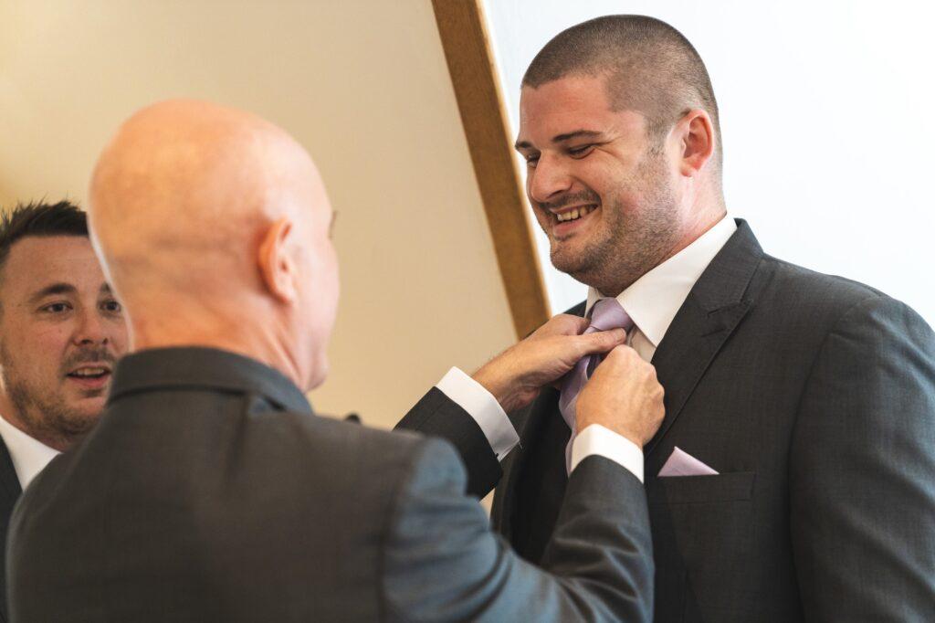 grooms tie adjusted groom prep cain manor venue surrey oxford wedding photography