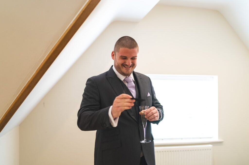 smiling groom holds champagne glass cain manor venue surrey oxfordshire wedding photography