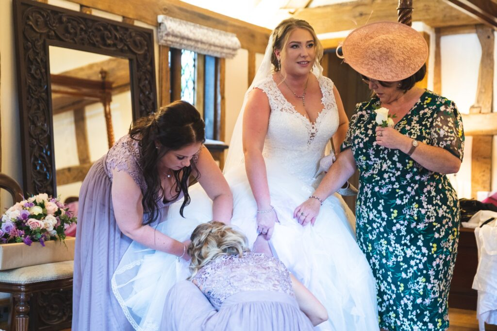 bride helped on with dress bridal prep cain manor venue surrey oxfordshire wedding photography