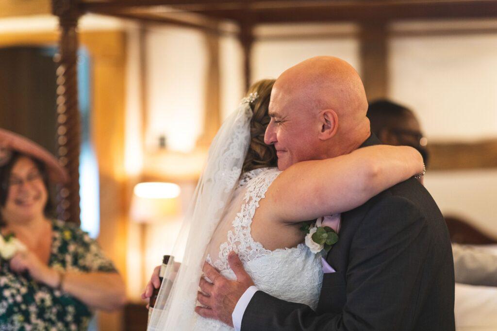 bride hugs father bridal prep cain manor venue surrey oxford wedding photography