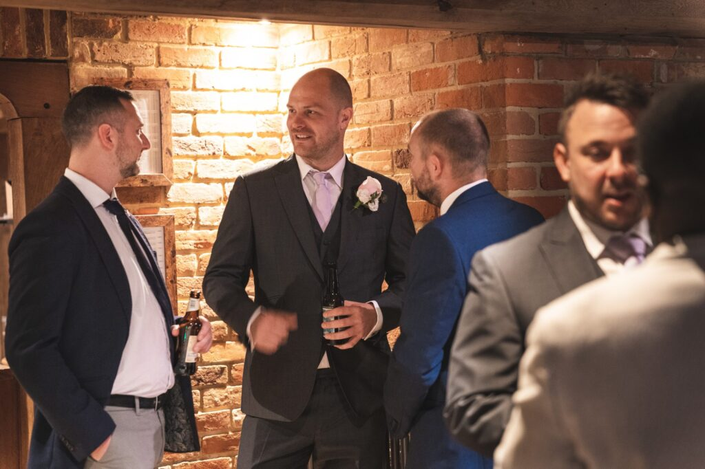 groom enjoys drinks before ceremony cain manor venue surrey oxford wedding photographer