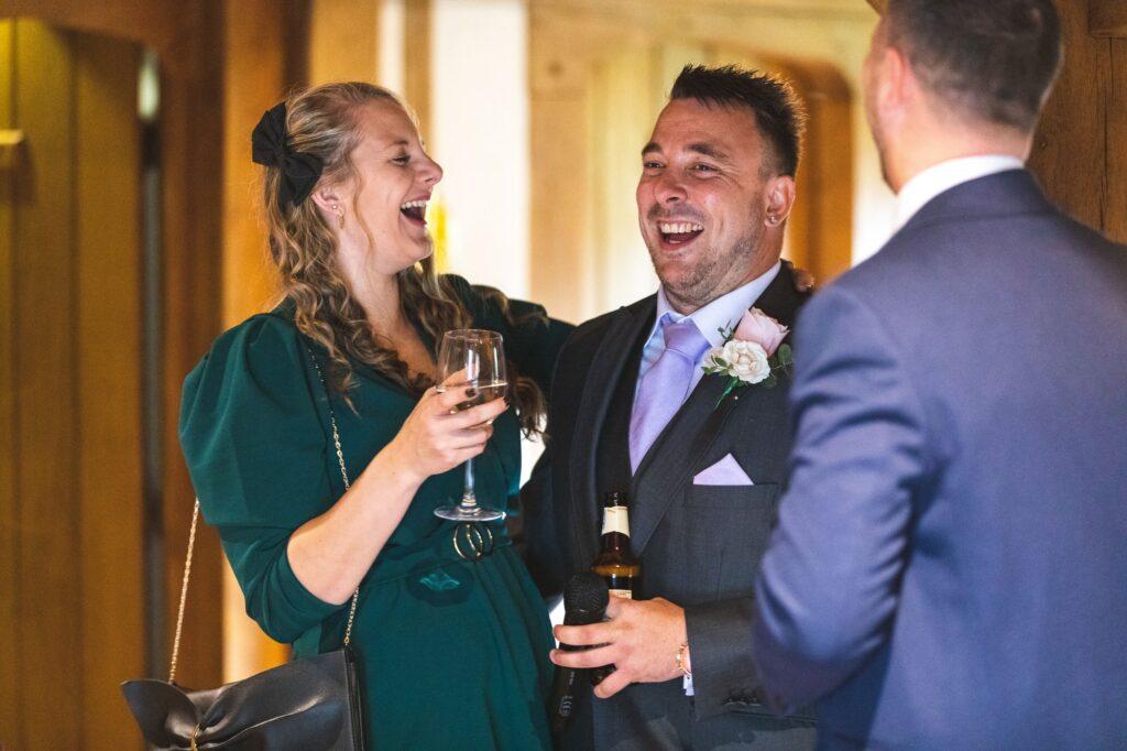 laughing best man enjoys drink cain manor surrey oxford wedding photographers