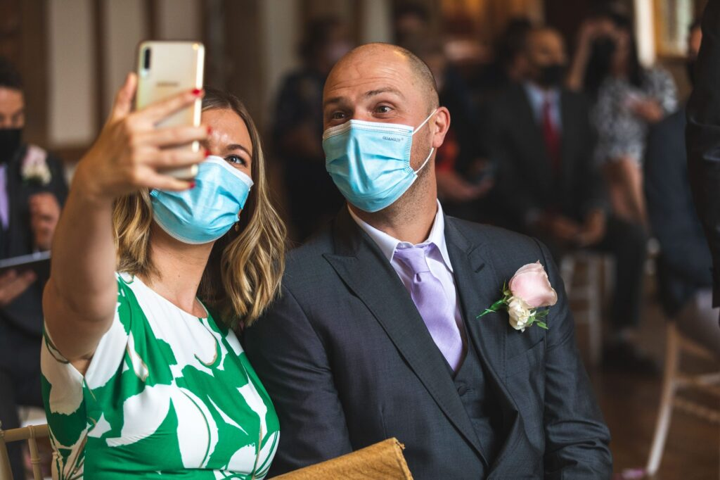 face covered guests take selfie cain manor marriage ceremony surrey oxford wedding photography