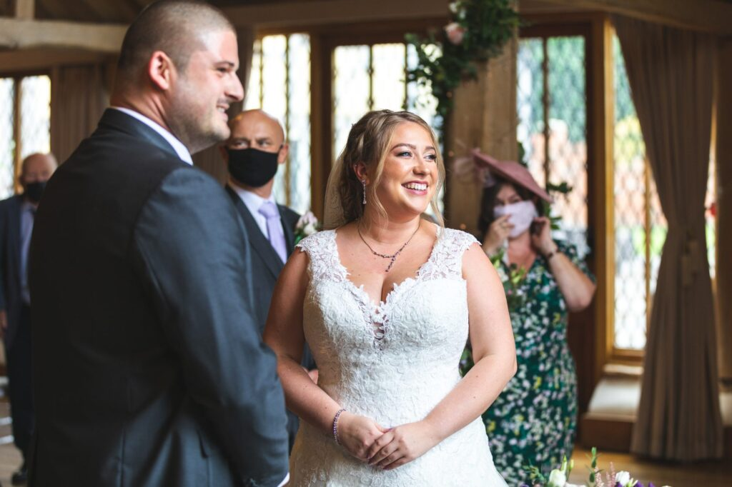 smiling bride groom hear celebrant cain manor ceremony surrey oxford wedding photographers