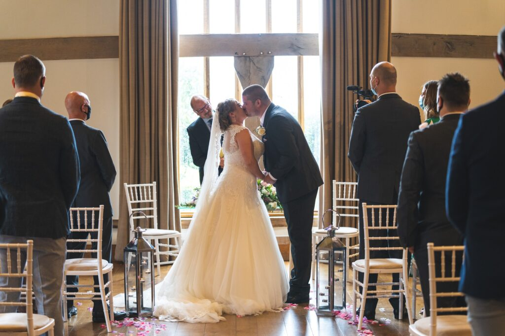 bride groom first kiss cain manor marriage ceremony surrey oxford wedding photographer
