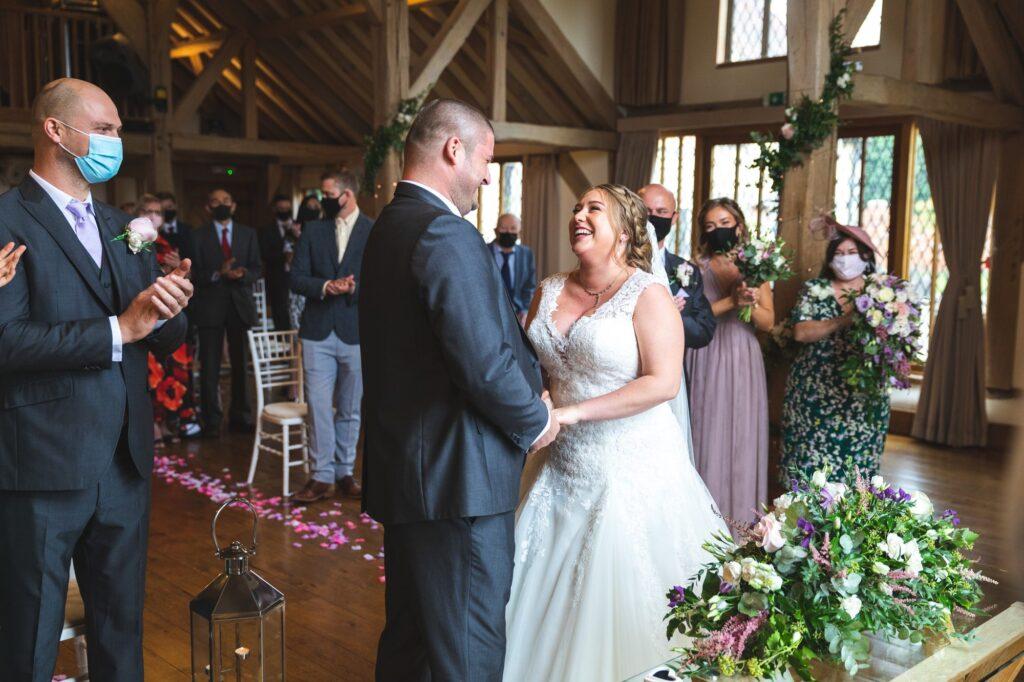 guests applaud bride groom cain manor marriage ceremony surrey oxford wedding photographers