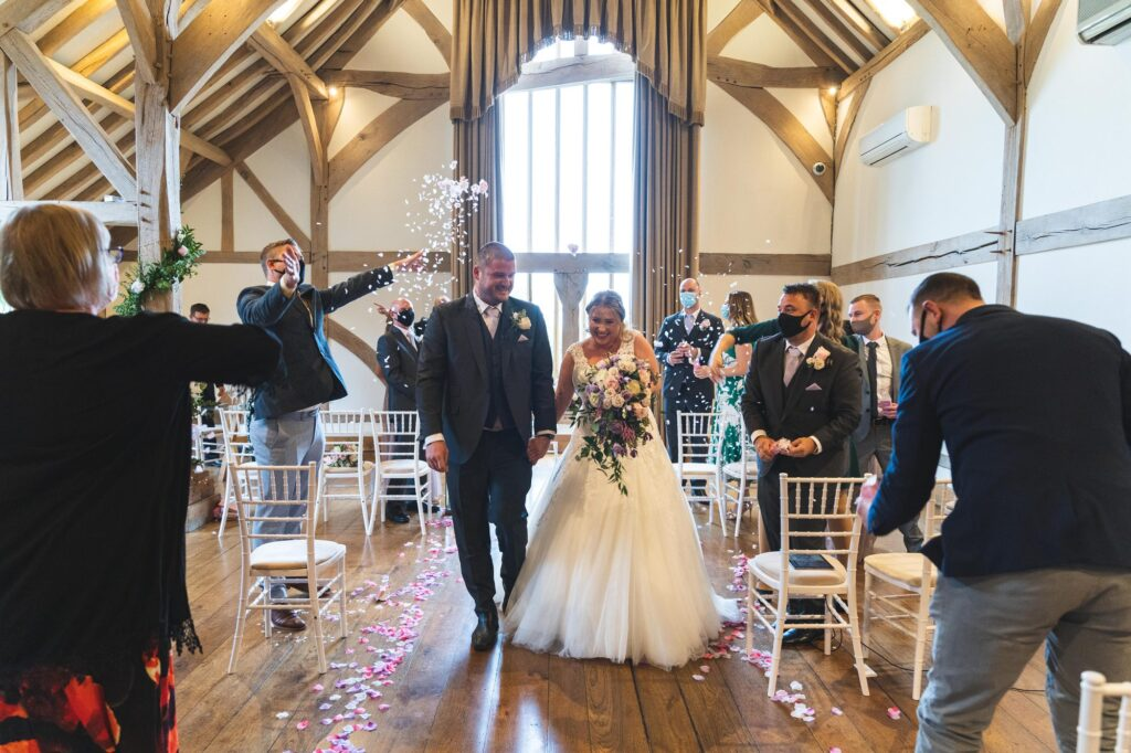confetti shower bride groom walk down aisle cain manor ceremony surrey oxford wedding photographer