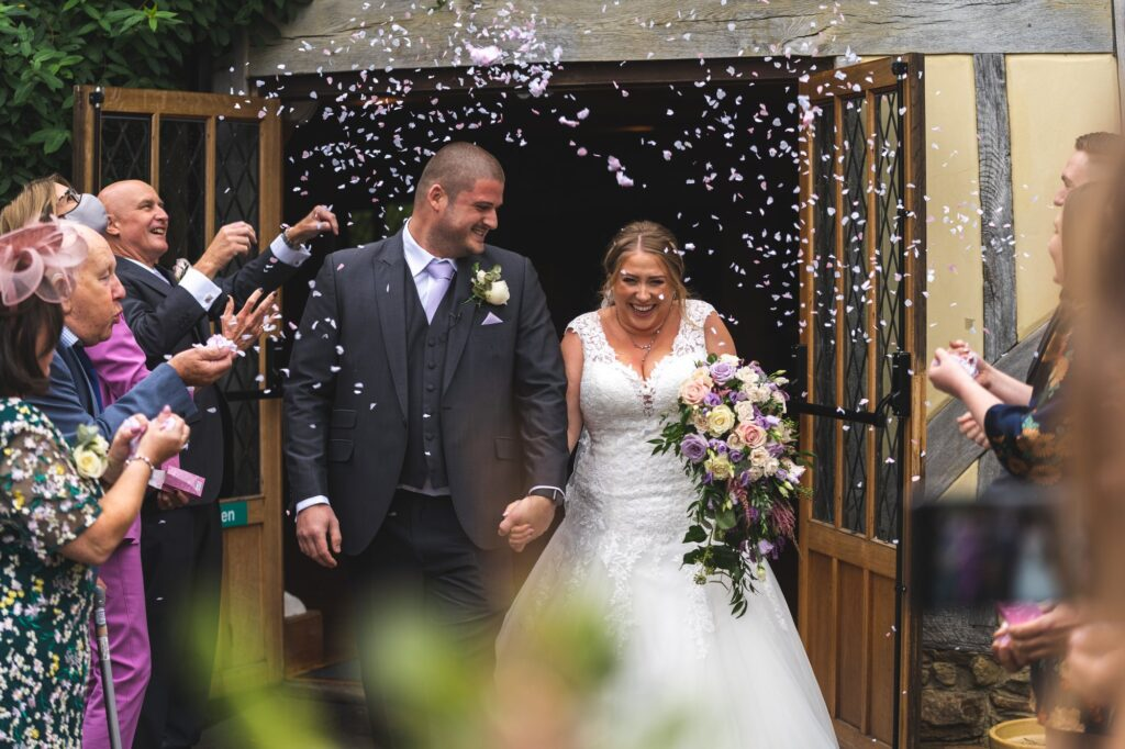 smiling bride groom confetti parade surprise cain manor surrey oxford wedding photographers