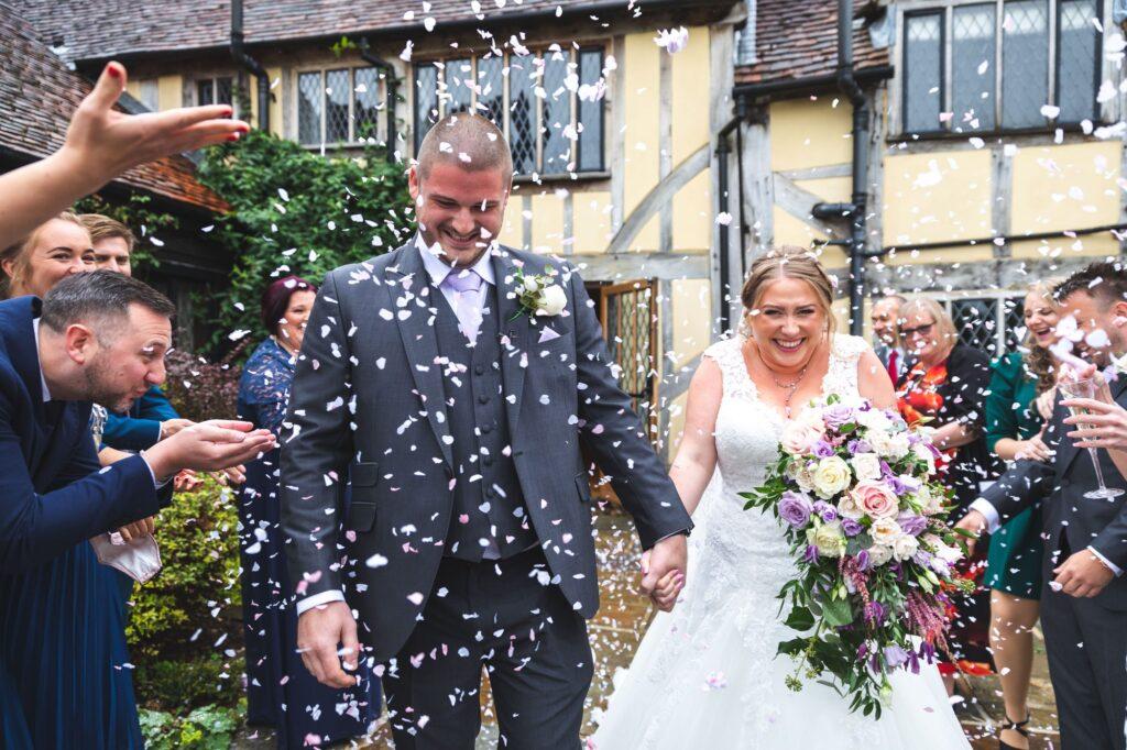 smiling bride groom enjoy confetti shower cain manor hampshire surrey borders oxfordshire wedding photographer