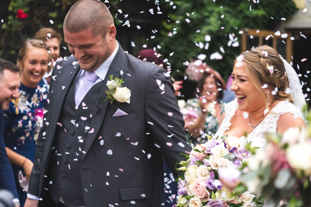 laughing groom bride guests enjoy confetti parade cain manor surrey oxfordshire wedding photographers