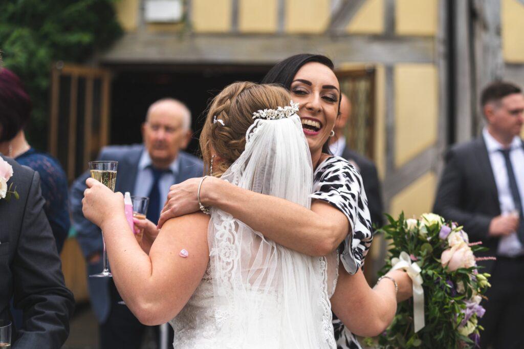 guest hugs bride champagne reception cain manor surrey oxford wedding photographer