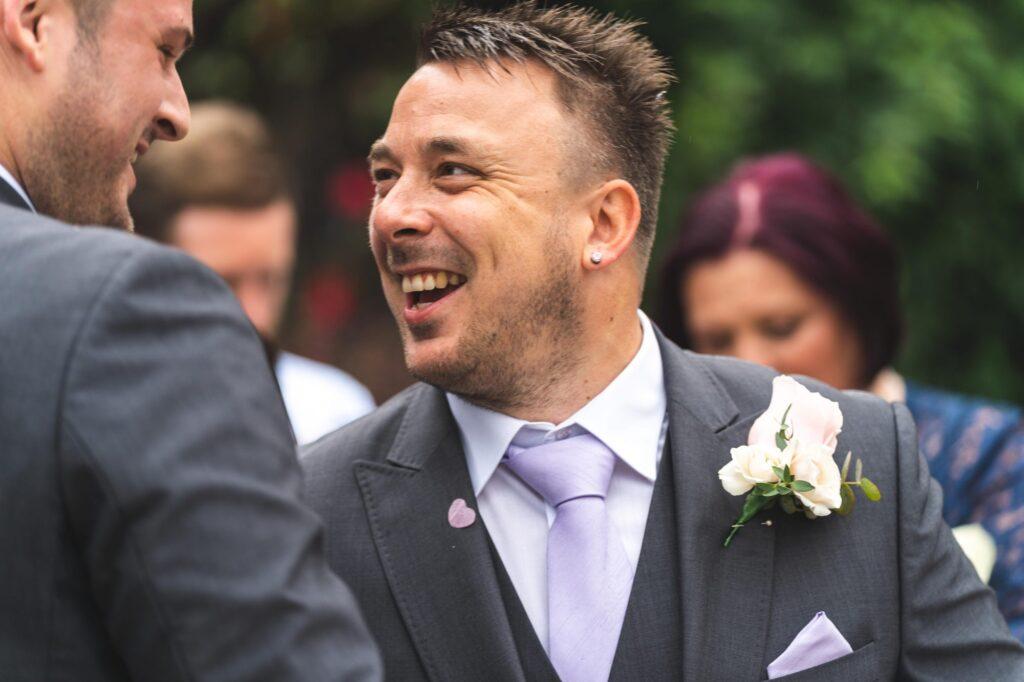 happy groom groomsman champagne reception cain manor surrey oxford wedding photographers