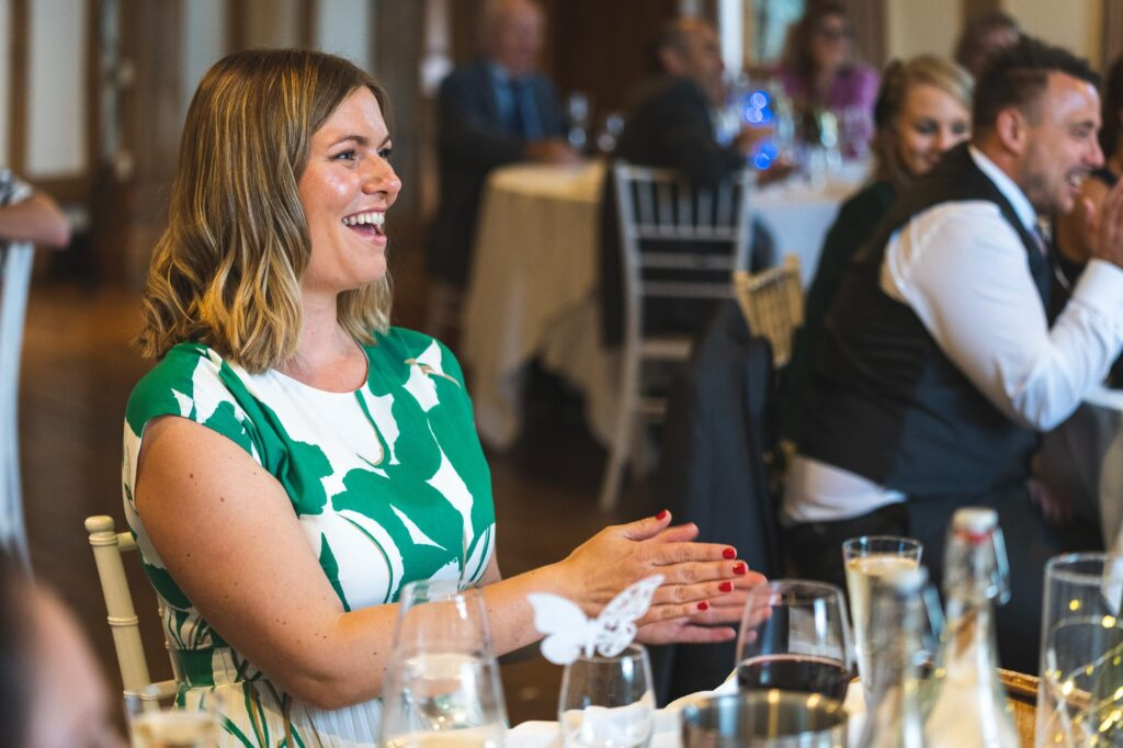 laughing reception guest applauds father of bride speech cain manor surrey oxford wedding photographers