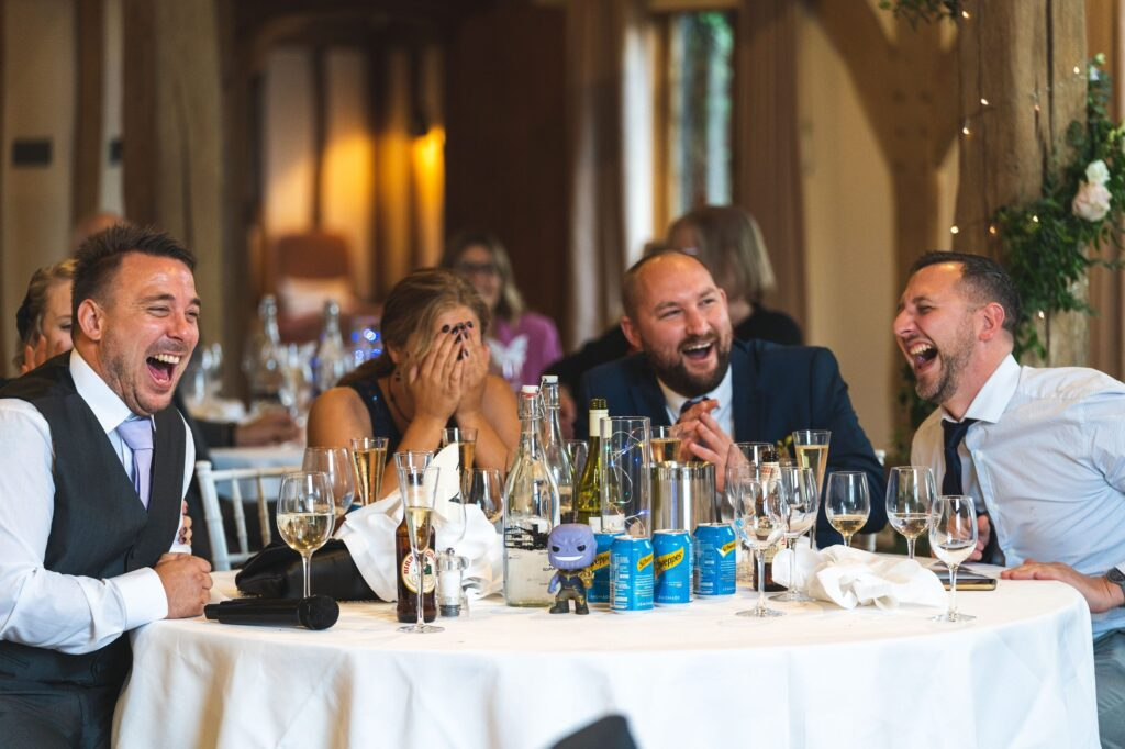 laughing guests hear speeches cain manor reception surrey oxfordshire wedding photographers