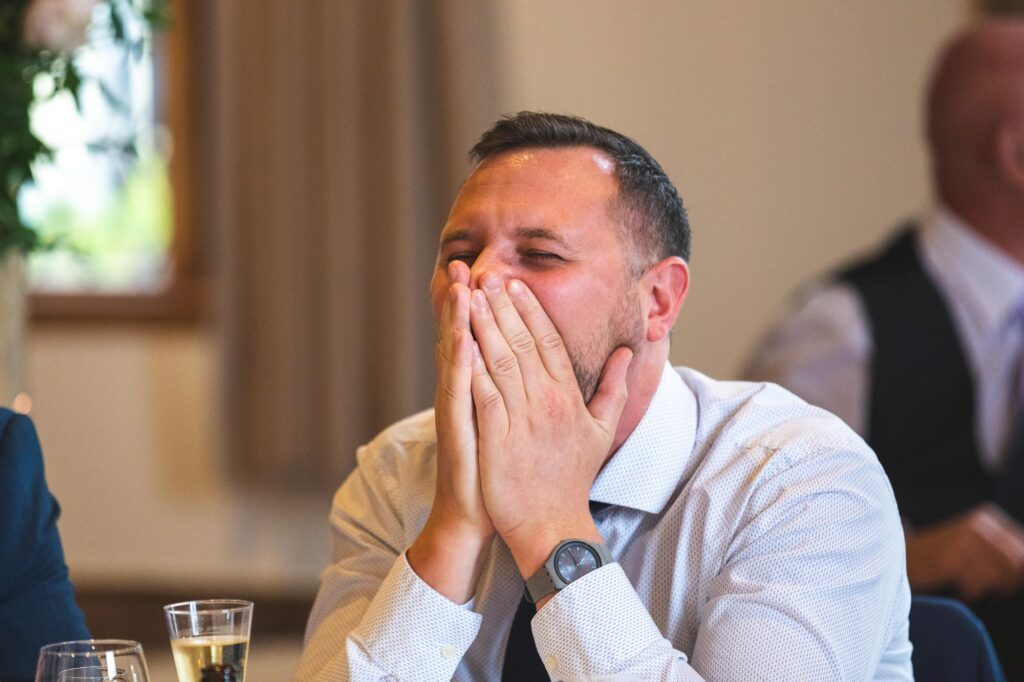 guest covers face hearing best mans speech cain manor reception surrey oxfordshire wedding photography