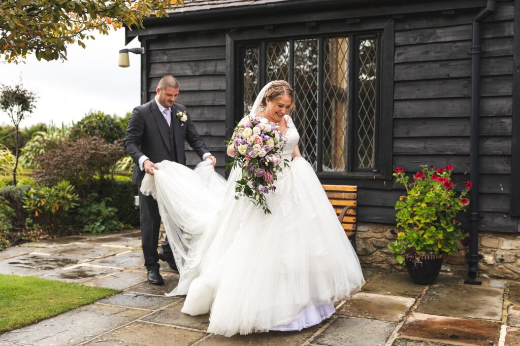 groom carries brides wedding gown train cain manor surrey oxford wedding photographer