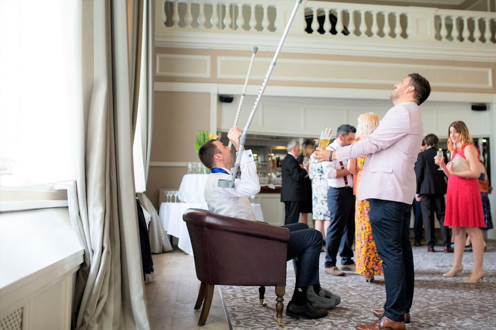 groom waves crutches de vere beaumont hotel windsor oxford wedding photography