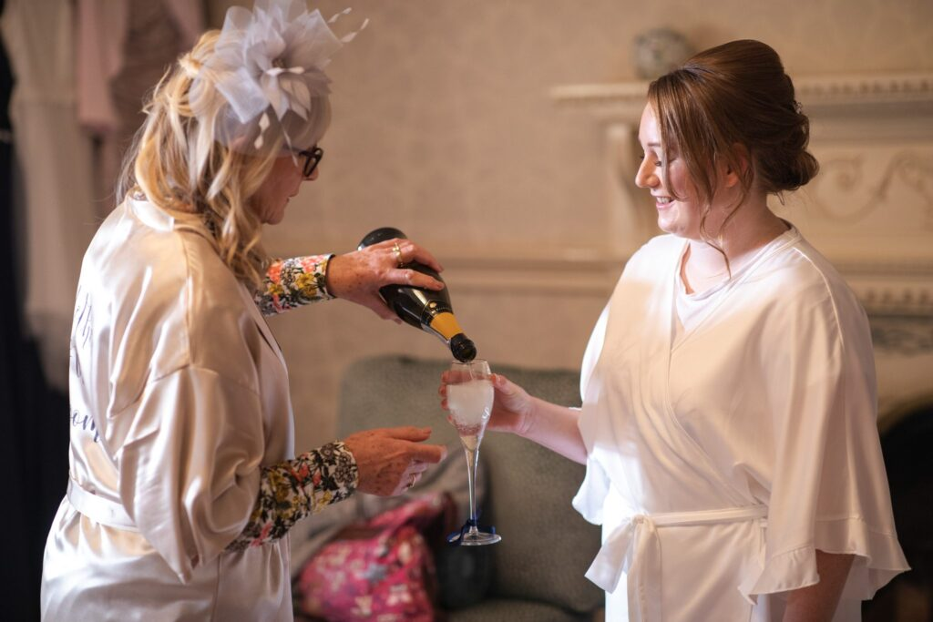 bride served champagne bridal prep hanbury manor ware hertfordshire oxfordshire wedding photography