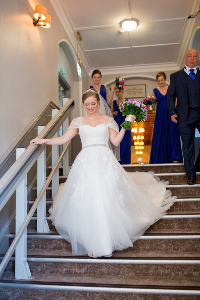 bride bridesmaids father of bride descend stairs de vere beaumont hotel windsor oxfordshire wedding photographer