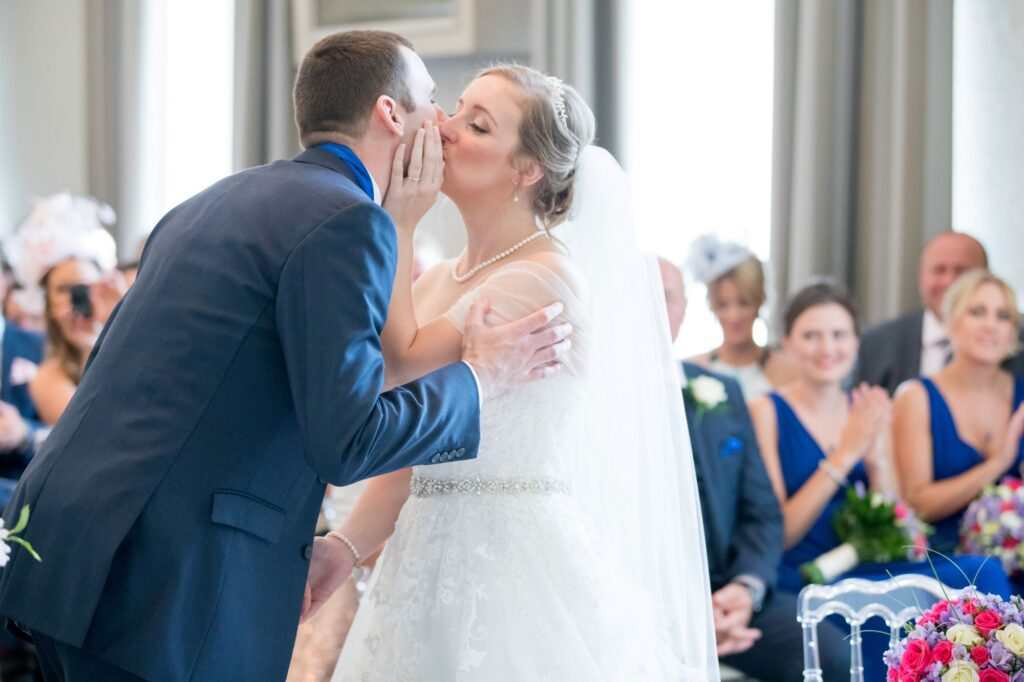 bride grooms first kiss marriage ceremony de vere beaumont hotel windsor oxfordshire wedding photographers