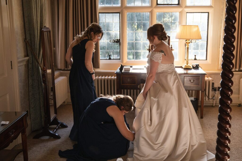bridesmaid adjust brides gown bridal prep hanbury manor ware hertfordshire oxfordshire wedding photographers