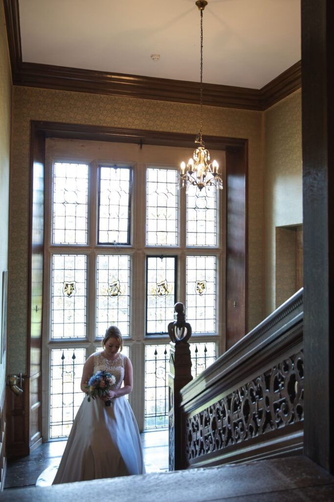 bride climbs carved staircase hanbury manor ware hertfordshire oxfordshire wedding photography