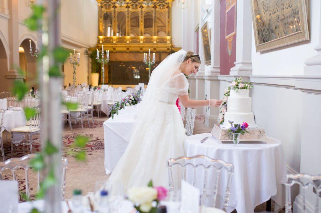 bride admires decorative cake de vere beaumont hotel windsor oxford wedding photographer
