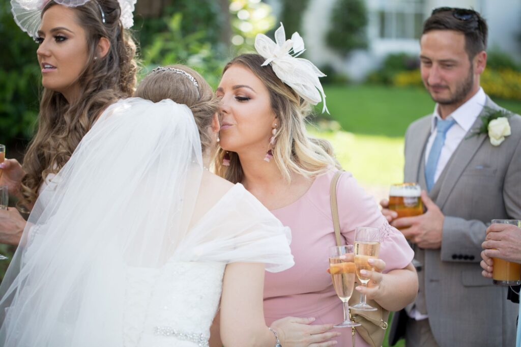 guest kisses bride champagne reception de vere beaumont hotel windsor oxfordshire wedding photographer