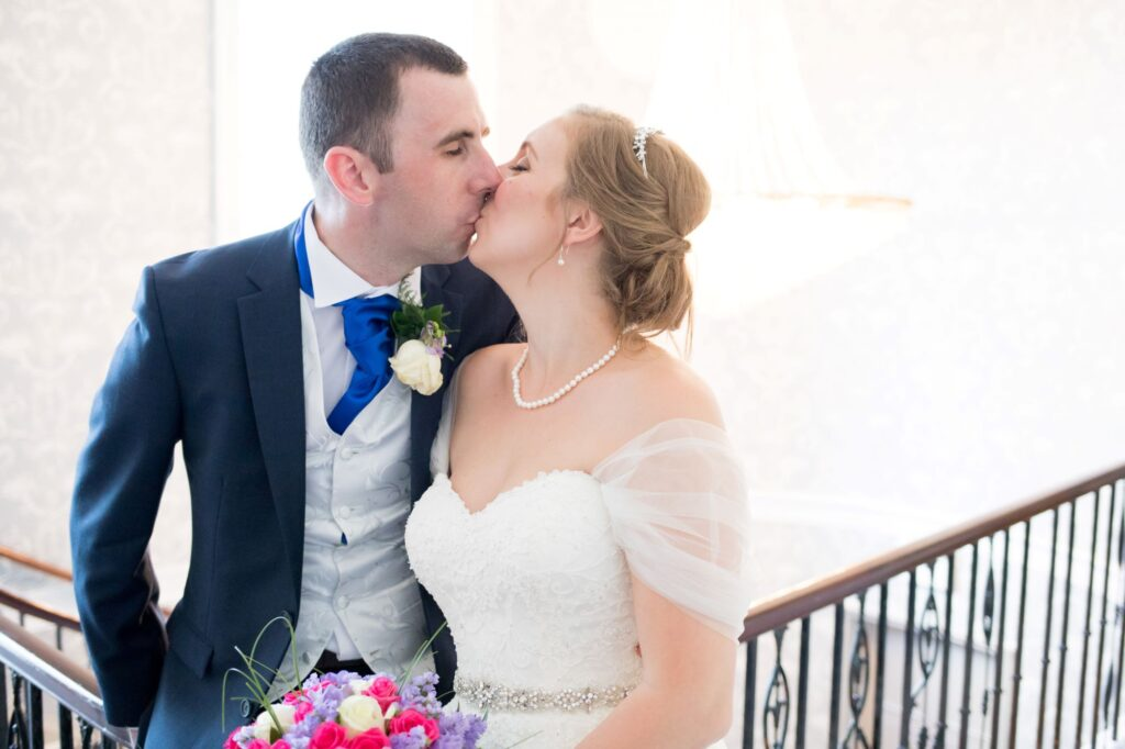 bride grooms staircase kiss de vere beaumont estate windsor oxfordshire wedding photography