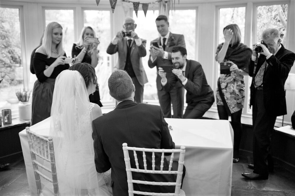 guests photograph bride groom signing marriage ceremony register bay tree hotel burford cotswold oxfordshire wedding photographers